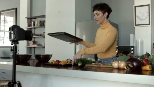 vidéos et rushes de vlogger recording video while cutting vegetables in kitchen - caméscope
