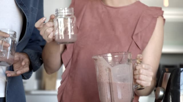 vloggers drinking smoothie while talking in kitchen - smoothie stock videos & royalty-free footage