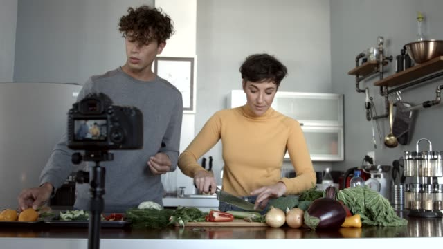 vidéos et rushes de vloggers preparing vegetables while filming in kitchen - services sociaux
