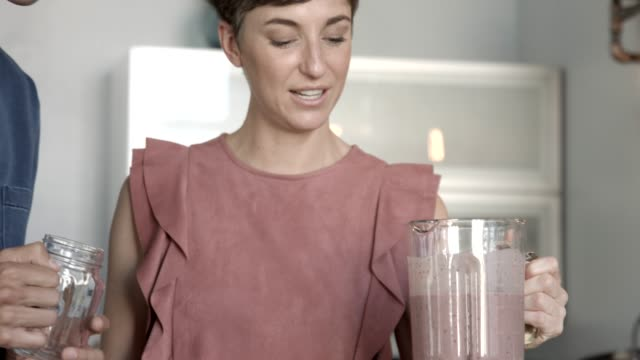 vloggers tasting smoothie while talking in kitchen at home - hushållsapparat bildbanksvideor och videomaterial från bakom kulisserna