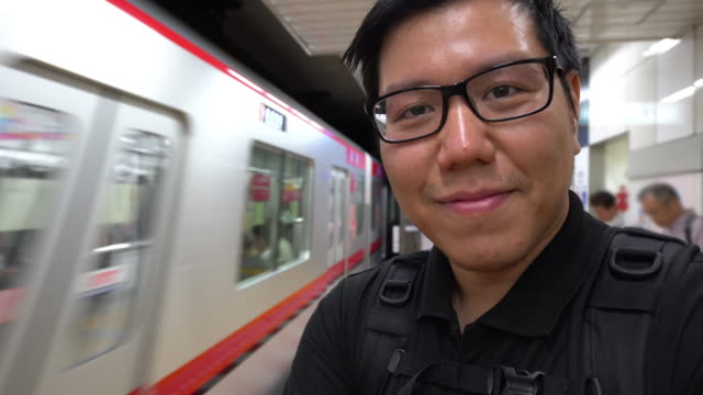 vlogging man standing while subway trains arriving. - railway station stock videos & royalty-free footage