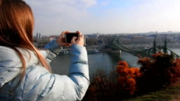 Vlogging: Young woman shoots video on the phone panorama of Budapest, Hungary