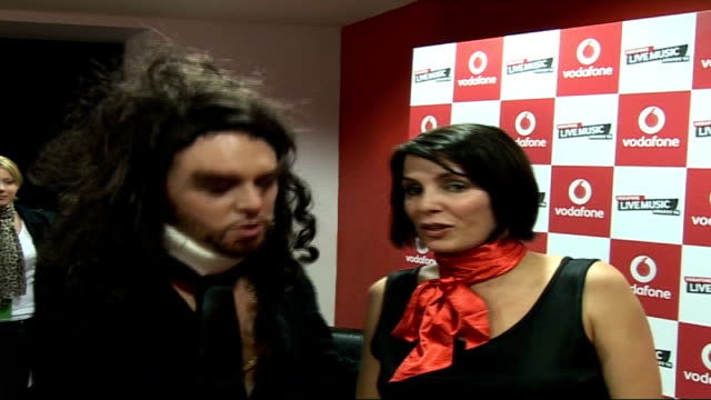 interviews and photocalls backstage Sadie Frost wearing black outfit and red scarf posing for photocall as joined Avid Merrion dressed as Russell...