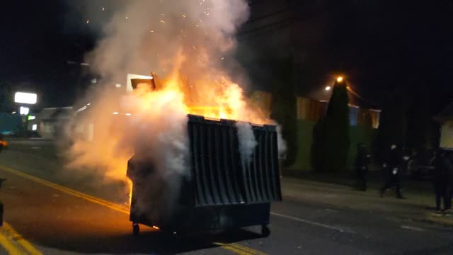 """stockvideo's en b-roll-footage met voice is heard singing """"america the beautiful"""" as a fire burns in a dumpster fire early in the morning after protests in the city on august 29, 2020... - afvalcontainer container"""