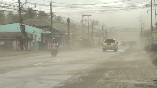 volcanic ash blows through air near busy highway after major eruption at taal volcano in philippines - taal volcano stock videos & royalty-free footage