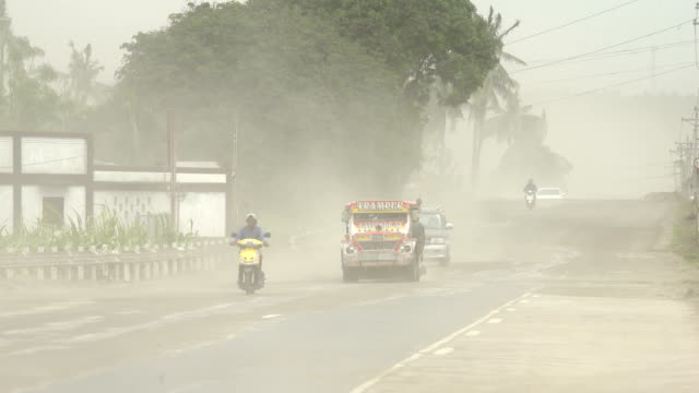 volcanic ash blows through air near busy highway after major eruption at taal volcano in philippines. - dust stock videos & royalty-free footage