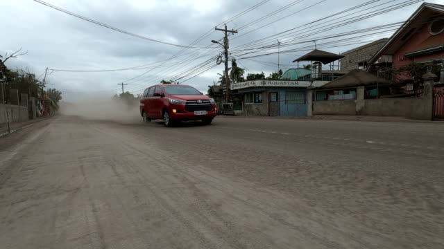 volcanic ash blows through air near busy highway after major eruption at taal volcano in philippines - major road video stock e b–roll
