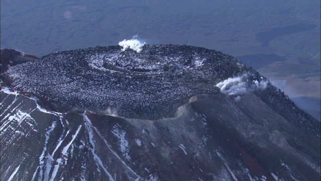 A volcanic crater on the Kamchatka Peninsula releases smoke.