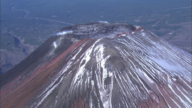 A volcanic crater releases smoke.