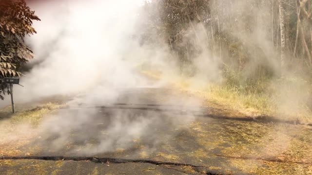 volcanic gases rise from cracks in the aftermath of eruptions from the kilauea volcano on hawaii's big island on may 6 2018 in pahoa hawaii - evacuazione video stock e b–roll