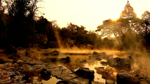 volcanic natural hot spring mineral water pool with steam spa and sun reflect light , travel landmark background ,lampang thailand landscape ,colorful dark tone