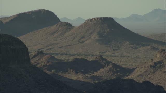 volcanic peaks in desert landscape - vulkanlandschaft stock-videos und b-roll-filmmaterial