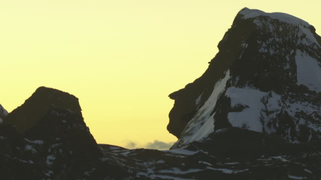 volcanic rock formation w/ patches of snow on top of mountain, side peak weathered in human face profile shape, yellow sky bg. no people, nordic,... - weathered stock videos & royalty-free footage