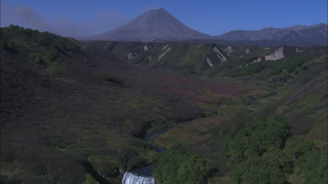 a volcano beyond a green valley spews ash. - wilderness stock videos and b-roll footage