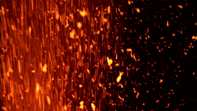 A volcano erupts and shoots lava into the night sky. Available in HD.