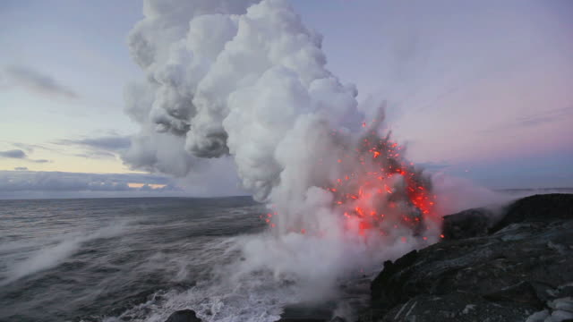 ws volcano exploding and forming steam cloud by ocean at dawn / kalapana, hawaii, usa - eruzione video stock e b–roll