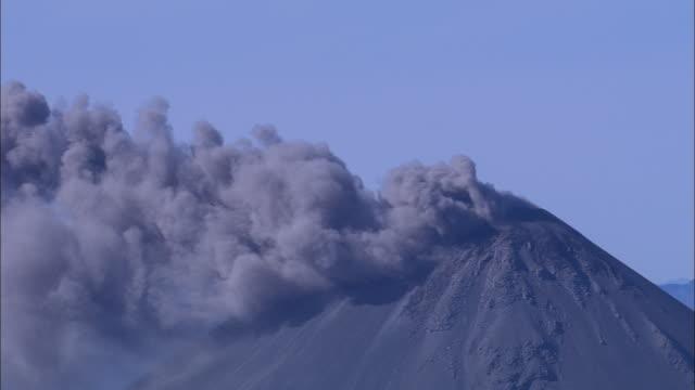 A volcano spews ash.