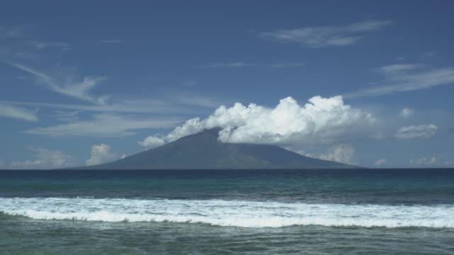 volcano with clouds from mainland, waves wash in, manam, papua new guinea, april 2009 - dom bildbanksvideor och videomaterial från bakom kulisserna