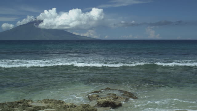 volcano with clouds from mainland, waves wash in, manam, papua new guinea, april 2009 - isola video stock e b–roll
