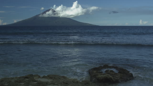 volcano with clouds from mainland, waves wash in, manam, papua new guinea, april 2009 - pyroklastischer strom stock-videos und b-roll-filmmaterial