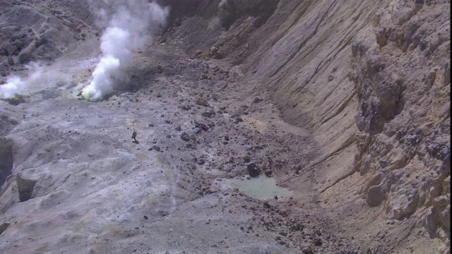 A volcanologist approaches a smoking volcano and crater.