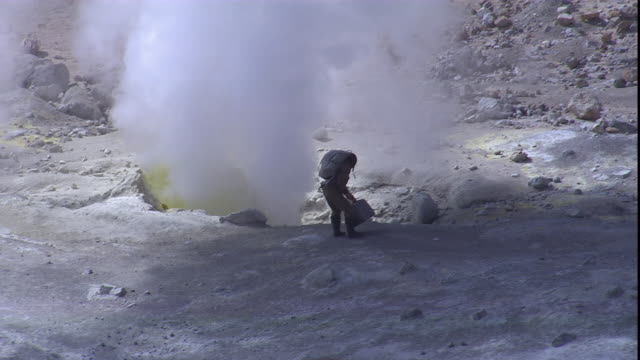 a volcanologist carries testing equipment to the edge of a smoking volcano. - geologist stock videos & royalty-free footage