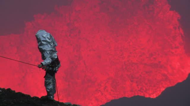 vídeos de stock, filmes e b-roll de volcanologist stands on cliff with large eruption of lava behind, marum volcano, ambrym island, vanuatu - inferno vida após a morte