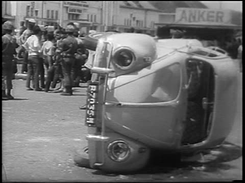 Volkswagen Bug overturned on street in antiChinese riot / Jakarta Indonesia / newsreel