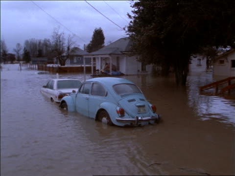 Volkswagen bug submerged in water on flooded suburban street