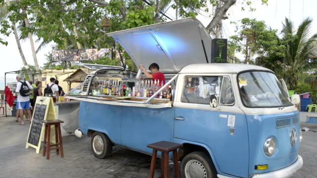 a volkswagen bus as bar in fisherman's village - bus stock-videos und b-roll-filmmaterial