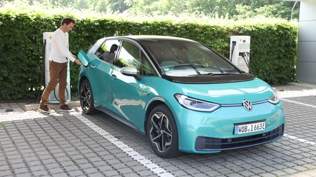 """volkswagen employee demonstrates the charging of a volkswagen id.3 electric car outside the """"gläserne manufaktur"""" production facility on june 08 in... - electricity stock videos & royalty-free footage"""