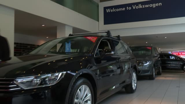 volkswagen shares fall over emissions scandal england london blurred shot of vw badge pull cars on display in showroom zoom in volkswagen sign sign... - バッジ点の映像素材/bロール