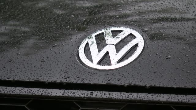 volkswagen shares fall over emissions scandal england london ext 'vw' logo on car bonnet cars at volkswagen dealership 'polo' on rear of car - ロゴマーク点の映像素材/bロール