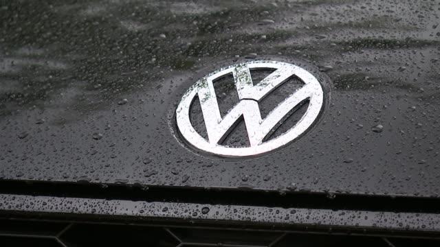 Volkswagen shares fall over emissions scandal ENGLAND London EXT 'VW' logo on car bonnet Cars at volkswagen dealership 'Polo' on rear of car