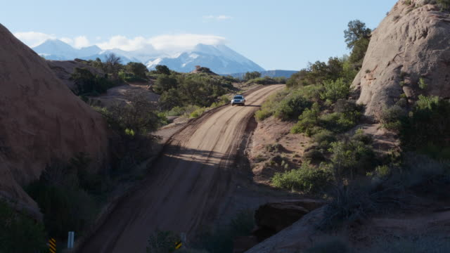 volkswagen suv climbing a steep hill on dirt road in moab utah - sports utility vehicle stock-videos und b-roll-filmmaterial