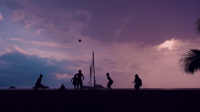 volleyball-silhouette auf sonnenuntergang strand - volleyballnetz stock-videos und b-roll-filmmaterial