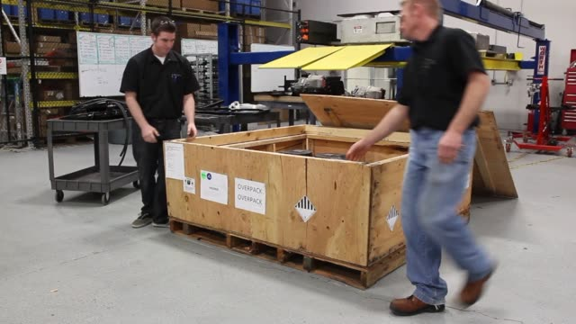A 350 volt battery pack sits in a crate waiting to be installed in a Chevrolet Express Van at the VIA Electric Motors labs as engineers work in the...