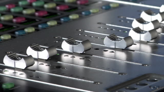 CU Volume sliders on sound mixing console in automated motion / New York City, New York, USA