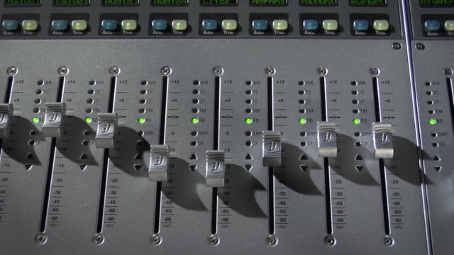 CU HA Volume sliders on sound mixing console in automated motion / New York City, New York, USA