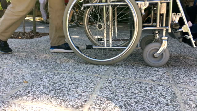 stockvideo's en b-roll-footage met vrijwilliger assistent senior volwassene te duwen op de rolstoel - woongemeenschap ouderen