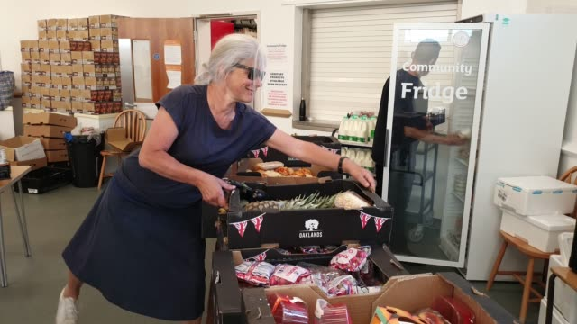 volunteer brings a box of vegetables into the albrighton community centre which partners with environmental charity hubbub to create the community... - brian dayle coronavirus stock videos & royalty-free footage