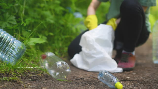 volunteer collects plastic bottles outdoors - garbage stock videos & royalty-free footage