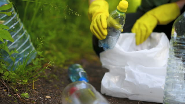 volunteer collects plastic bottles outdoors - hd format stock videos & royalty-free footage