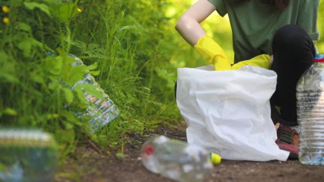 freiwilliger sammelt plastikflaschen im freien - menschliche gliedmaßen stock-videos und b-roll-filmmaterial
