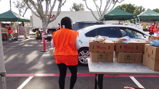 volunteer dancing while distributing packages at food bank drive-through event in baldwin park, california, u.s., on wednesday, january 13, 2021. - giving stock videos & royalty-free footage