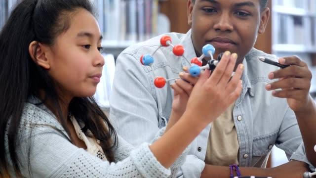 volunteer elementary school tutor helps student with science homework - atom stock videos & royalty-free footage