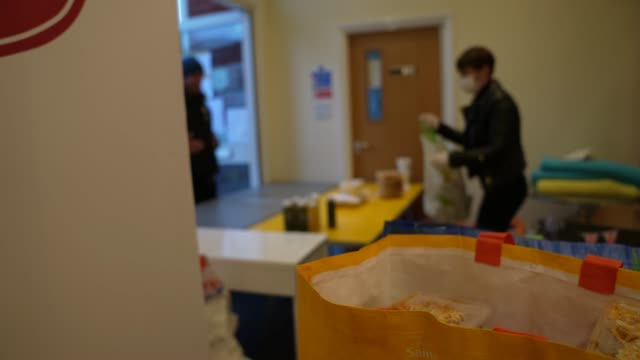 volunteer from ealing soup kitchen hands over a food parcel to a client on march 30, 2020 in london, england.the coronavirus pandemic has spread to... - soup kitchen stock videos & royalty-free footage