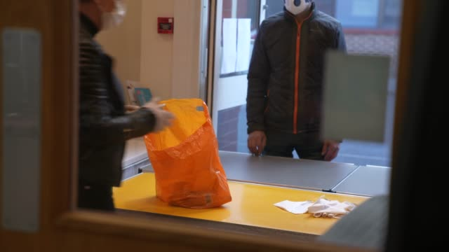 a volunteer from ealing soup kitchen hands over a food parcel to a client on march 30 2020 in london englandthe coronavirus pandemic has spread to... - soup kitchen stock videos & royalty-free footage