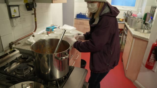 a volunteer from ealing soup kitchen prepares food parcels for clients on march 30 2020 in london englandthe coronavirus pandemic has spread to many... - soup kitchen stock videos & royalty-free footage