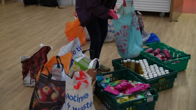 a volunteer from ealing soup kitchen prepares food parcels for clients on march 30 2020 in london englandthe coronavirus pandemic has spread to many... - homelessness stock videos & royalty-free footage